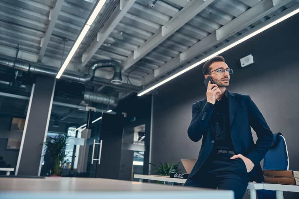 Happy entrepreneur answers the call while standing at the office